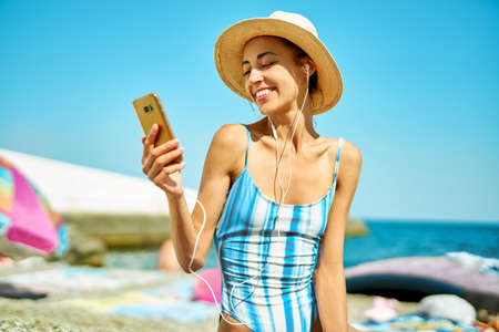 happy woman in straw hat and swimsuit at beach communicating on smartphone, online video cell phone call. Technology and communication during summer vacation Imagens - 151073287
