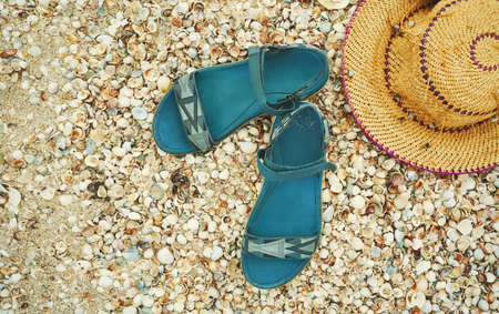 Straw hat and sandal on beach. Top view summer accessories on seashells texture. Tropical summer vacation concept Imagens