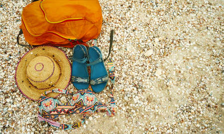 Top view beach accessories on seashells. Straw hat, orange bag, sandals and swimwear on beach. Background with copy space and visible seashells texture.