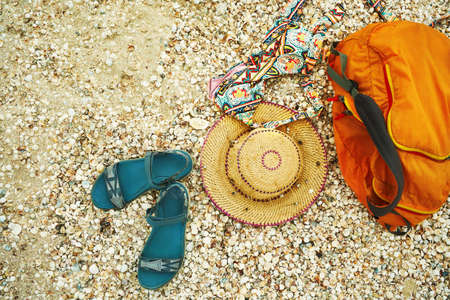 Sandal, straw hat, swimwear and orange bag on seashells background, top view. Female beach accessories for summer beach vacation Imagens - 151886311
