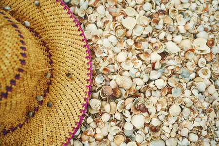 close-up straw hat on seashells beach. Background with copy space and visible seashells texture. Imagens