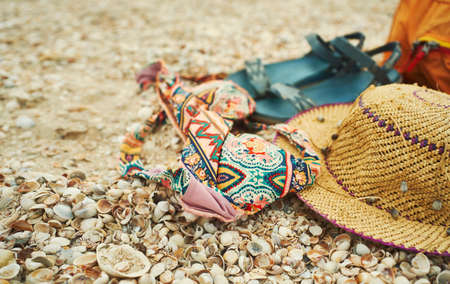 Close-up woman vacation set, beach accessories on seashells. Summer concept of beach, straw hat, bikini and sandals