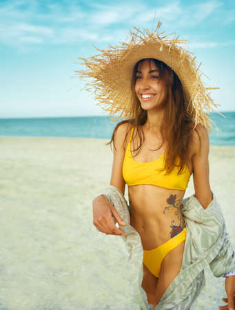 Beautiful smiling latin woman in bright yellow bikini and straw hat walking on beach by ocean seashore. Stylish girl enjoying summer tropical vacation at sea. Imagens - 152425084