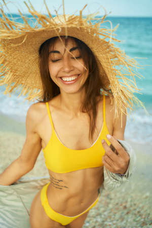 Summer lifestyle portrait of pretty young woman on tropical sand beach, laughing and feeling happiness by seaside. Trendy girl in yellow bikini and big straw hat Imagens - 152427080