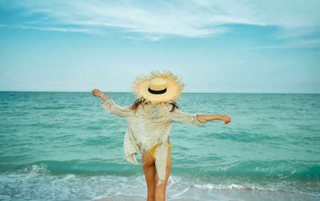 Beach summer stylish girl in happy freedom concept standing back with open arms by blue ocean with waves, enjoying sea breeze. Woman in big straw hat on windy beach, rear view Imagens - 152424959