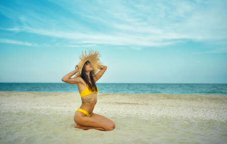 Beautiful tanned woman on tropical beach by ocean with copy space. girl wearing in yellow bikini and big straw hat sits on sand, breathing and enjoying sea breeze