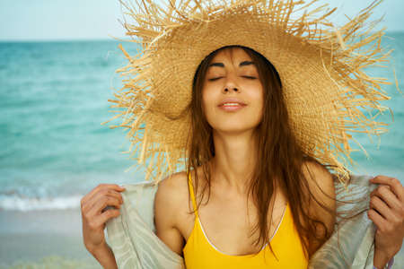 Close-up outdoors fashion portrait young woman wearing big straw hat by sea on tropical beach, breathing and enjoy the summer water breeze