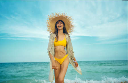 Joyful happy travelr woman in fashionable swimwear and straw hat goes on camera wiht sea view on background. tourism and sea resort, latin woman on vacation Imagens - 152956319