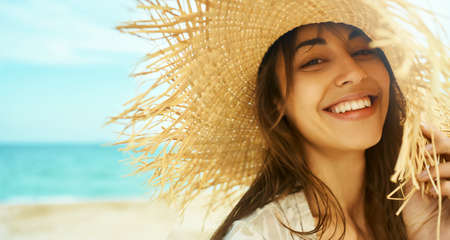 Close-up face smiling woman wearing straw hat at beach in sunshine sunrise on seashore. Happy tanned travel woman laughing and looking to camera. relaxing at beach
