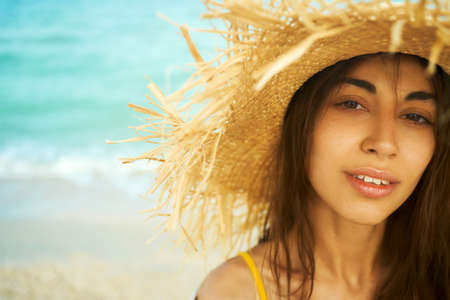 close-up face beautiful traveler woman in straw hat at beach by ocean. looking to camera and relaxing at beach. summer holiday vacation Imagens - 152956323