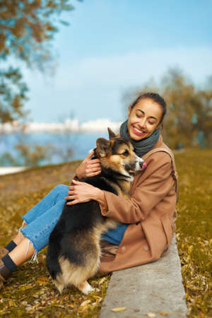 Autumn pet walking. woman in coat hugs cute Welsh Corgi dog in autumn park, cute moments with pets. autumn concept and friendship dog and human