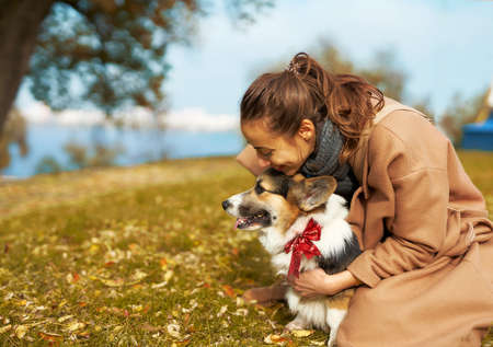 Autumn woman in coat tenderly embracing Welsh Corgi dog in autumn park, cute moments with pet. autumn wakks concept, friendship dog and human Imagens