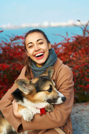 Bright autumn portrait happy laughing girl with her pet Welsh Corgi dog on red fall leaves background at sunny autumn day Imagens - 153423114