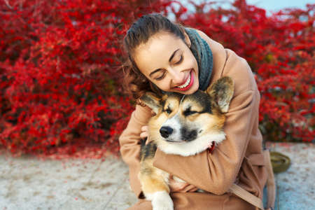 Cute moments woman embracing her lovely pet Welsh Corgi dog on autumn nature background with red fall leaves. spending time together outdoors at sunny autumn day.