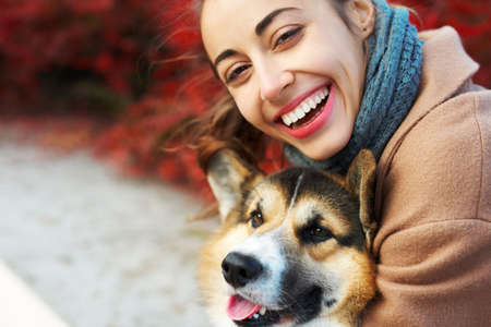 close-up autumn portrait happy woman and pet Welsh Corgi dog with funny face on red fall leaves background. spending time together outdoors at sunny autumn day Imagens