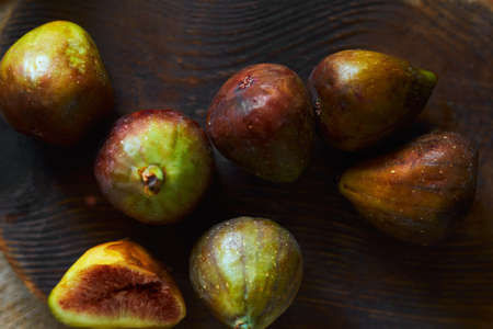 flat lay fresh sweet figs on dark wooden cutting board, close-up top view