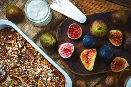 Top view baked delicious fruit pie with figs on breakfast with yogurt. Fresh whole and cuting figs on wooden cutting board on old wooden table background