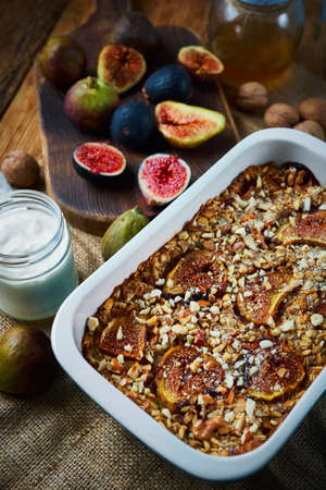 Homemade healthy autumn breakfast, baked oatmeel with figs and nuts, yogurt and fresh figs on wooden craft table on kitchen