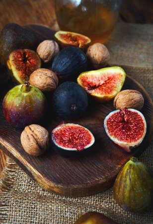 Autumn seasonal vitamin food. Fresh figs whole and sliced, walnuts, honey on craft kitchen background Imagens