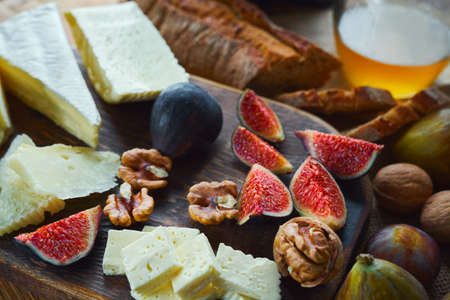 Cheese with figs and walnuts on wooden cutting board on wooden table. Bread and honey on background. Concept autumn food and snacks.