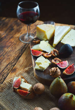 Delicious cheese mix with figs and walnuts. Tasting dish on a wooden cutting board. Food for red wine. Autumn food and snacks concept