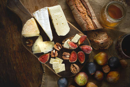 Flat lay meal and snacks for wine. Assortment of cheeses, glass red wine, figs, honey, nuts and bread on wooden table. Top view.