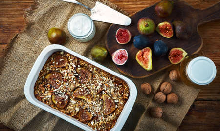 Flat lay healthy breakfast on old wooden table. Homemade crumble pie with figs, yogurt, walnuts, fresh figs on craft cutting board. Concept autumn home bakery.