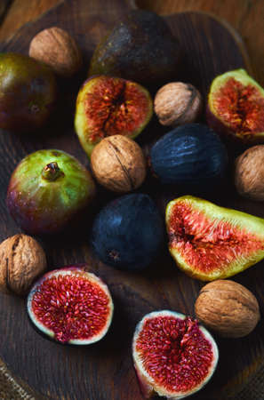 fresh sweet figs whole and sliced with walnuts on craft wooden cutting board. Autumn seasonal vitamin food. Imagens