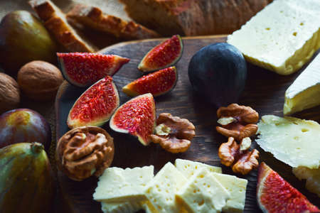 close up food image cheese with figs and walnuts on wooden cutting board on wooden table. Concept autumn food and snacks. Imagens