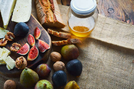 cheeseboard, fresh figs, whole wheat breadand and honey on sackcloth on table. Food for red wine. Autumn food and snacks concept Imagens - 154474719