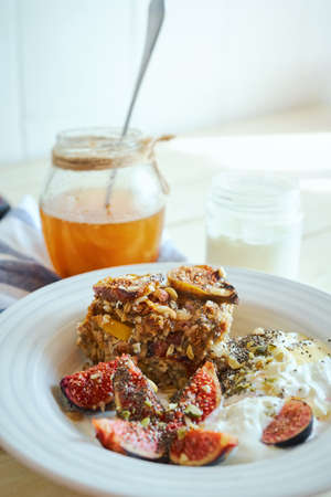 Healthy breakfast at home in morning, cozy food image baked oatmeel with figs, yogurt and and honey on white kitchen table. Concept home bakery recipe ideas. Imagens - 154474722