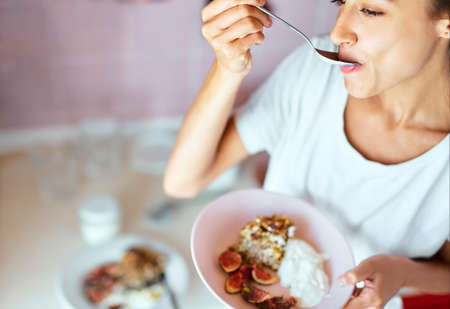 woman eating her homemade healthy breakfast at kitchen, fruit pie with figs and yogurt in plat. Kitchen or bakery poster design. Imagens - 154474725