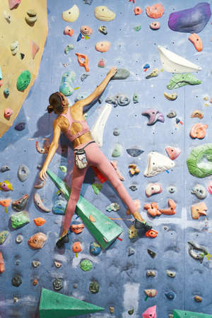Sporty woman with fit body climbs up the wall in a bouldering gym. Back view rock climber girl workout, execute exercise on climbing gym wall. Imagens