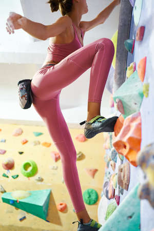 woman climber in silhouette in bouldering gym, sporty girl in pink sportswear mooving up on climbing wall, traning and execute exercise Imagens - 155062811