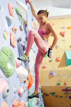 Young fit body woman climber lead climbing in gym, makes moves on sport route on bouldering wall. Workout, sport, active lifestyle. Focuc on leg. Imagens