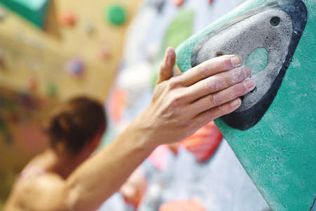 Close-up climber hand in chalk powder gripping hold. Woman climbing and exercising at indoor climbing gym wall Imagens - 154793408