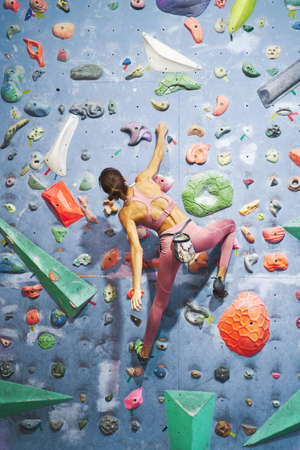 Exercising muscular woman rock climber training in climbing gym. Rear view muscular back sporty woman on bouldering wall. Sport, hobby, healthy lifestyle. Imagens
