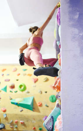 bottom view sporty woman climbing up in gym, gripping hold. Workout, sport, active lifestyle. Focuc on leg. Imagens - 154793367