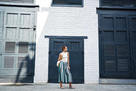 Lifestyle fashion portrait young stylish woman with backpack stands against white wall and big black doors on sides, urban street image Imagens - 154780790