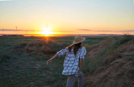 Candid shot traveler hipster woman walking on hills to see view of sunset, relaxing alone outdoors in nature. rear view