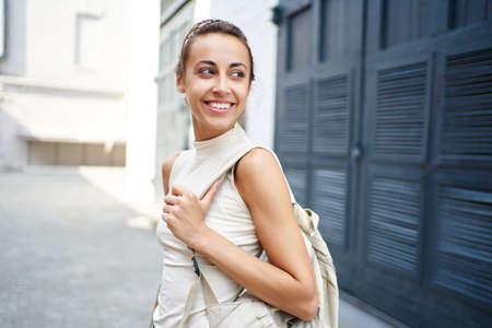 Close-up portrait of joyful woman smiling and looking away on urban street background. Beautiful female model with copy space. Imagens - 154779867