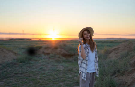 Candid shot happy girl in hat enjoying sunset alone outdoors in nature. Travel lifestyle emotional concept adventure