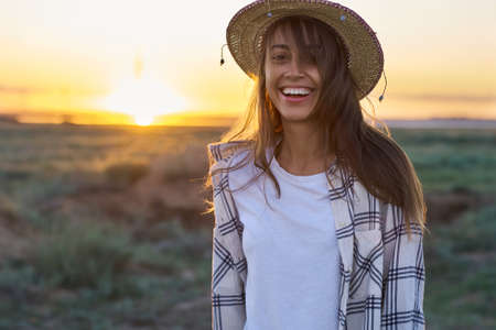 Emotional portrait happy hipster woman on sunset in nature view. Hipster treveler girl in hat in golden sun rays on background. wanderlust travel concept