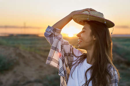 side view portrait happy hipster woman on sunset in nature view. Hipster treveler girl putting on hat in golden sun rays on background. wanderlust travel concept