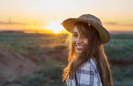 outdoors portrait young woman in hat smiling to camera in sun rays at sunset meadow. Travel autumn holidays, adventure, candid shot. Imagens