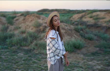 young traveler woman in stylish hat enjoying desert nature in meadow with copy space, sensual model with closing eyes outdoors, admiring nature Imagens