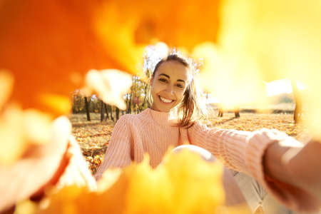 Delighted smiling girl makes selfie from frame witn fall leaves, enjoyng autumn sunny day at park