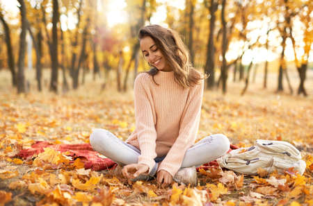 pretty woman in cozy sweater in autumn park with fall colorful background, sitting on blanket. Fall season concept. Outdoor lifestyle portrait.