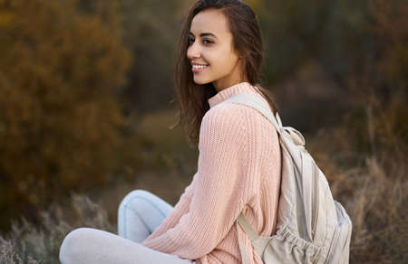 Closeup portrait woman in warm cozy sweater with backpack sitting and admiring nature in autumn forest. Fall season concept.