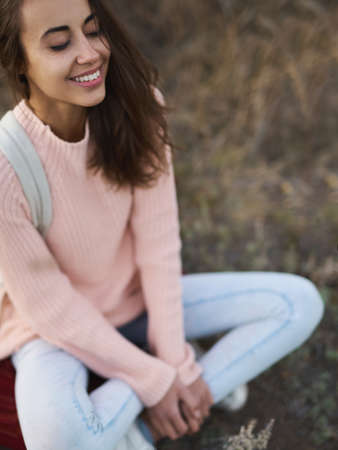 outdoor portrait woman with charming smile in warm cozy sweater sitting with closing eyes and enjoying nature in autumn forest. Fall season concept. Imagens